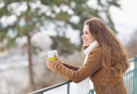 Young woman drinking hot beverage and looking into distance in winter park Stock Photo - 17797385