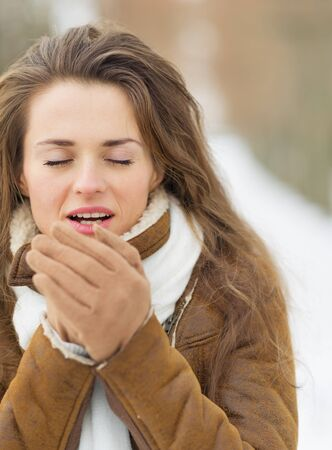 Young woman warming hands in winter outdoors Stock Photo - 17797380