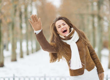 Happy young woman in winter jacket saluting outdoors Stock Photo - 17797382