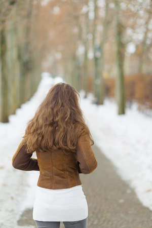 Young woman walking in winter park. rear view Stock Photo - 17797417