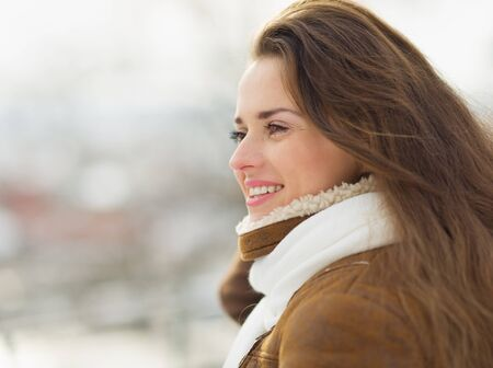 Portrait of happy young woman looking on copy space in winter outdoors