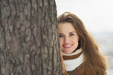 Portrait of happy young woman leaning against tree in winter park Stock Photo - 17797389