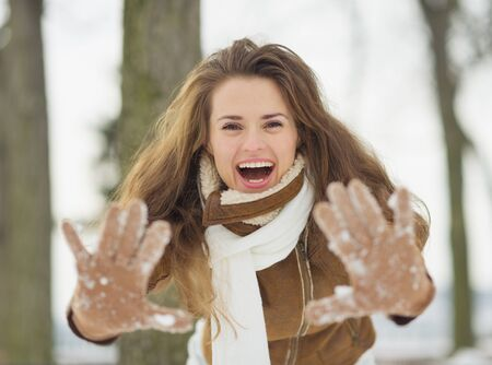 Happy young woman showing hands in snowed gloves in winter park Stock Photo - 17797381