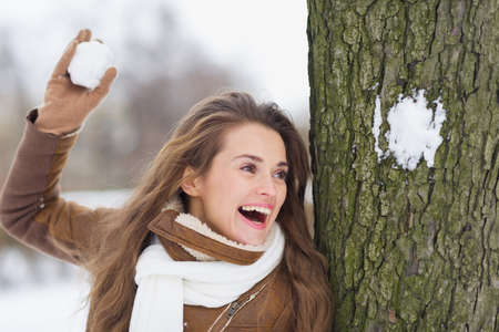 Happy young woman playing in snowball fights Stock Photo - 17797433