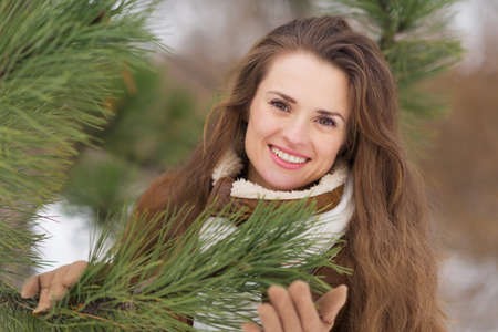 Portrait of happy young woman near spruce in winter outdoors Stock Photo - 17797432