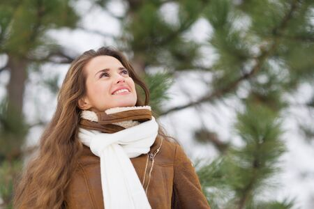 Happy young woman looking up on copy space in winter outdoors Stock Photo - 17797421