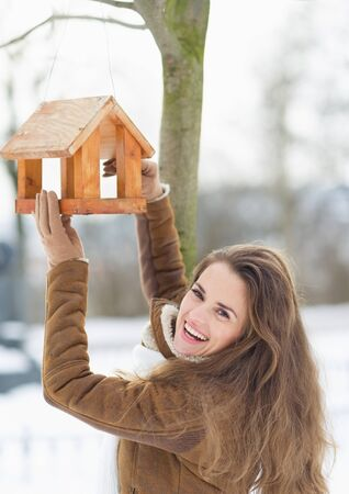 Smiling young woman hanging bird feeder on tree in winter outdoors Stock Photo - 17797414
