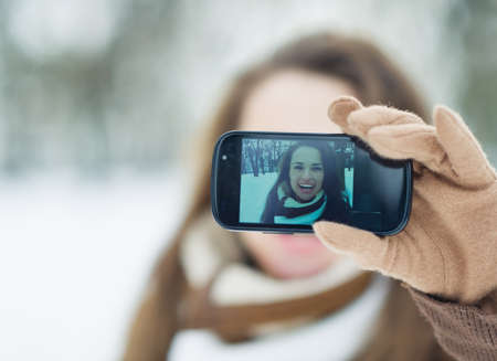 Happy young woman making self photo in winter outdoors photo