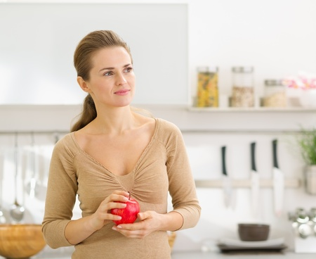 sagacious: Portrait of thoughtful young woman with apple in modern kitchen Stock Photo