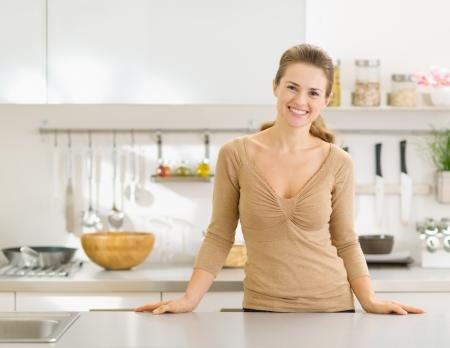 ama de casa: Retrato de la sonrisa joven ama de casa en la cocina moderna
