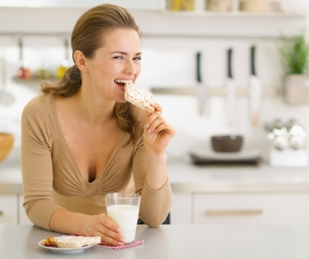 Young woman eating snacks in modern kitchen Stock Photo - 17800073