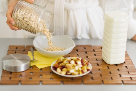Closeup on woman putting oatmeal into plate