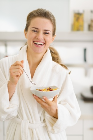 Happy young woman in bathrobe eating healthy breakfast Stock Photo - 17800111
