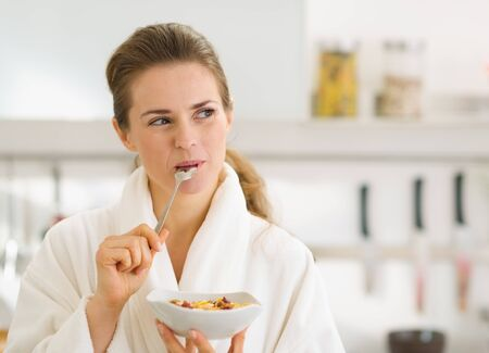 Happy young woman in bathrobe eating healthy breakfast Stock Photo - 17800067