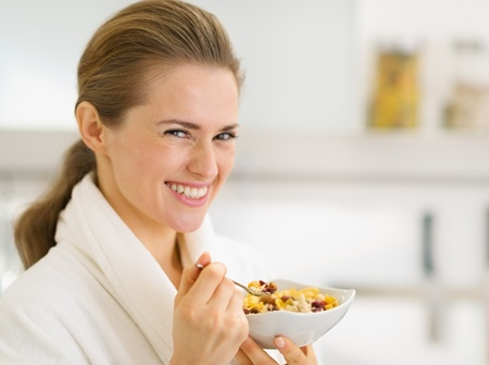 Portrait of happy young woman in bathrobe eating healthy breakfast Stock Photo - 17800070