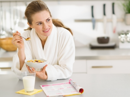 sagacious: Thoughtful young woman in bathrobe eating breakfast in kitchen