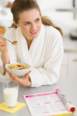 Thoughtful young woman in bathrobe eating breakfast in kitchen photo