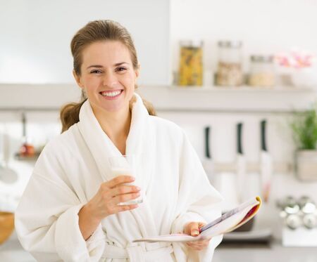 Happy young woman in bathrobe with glass of milk and magazine Stock Photo - 17800064