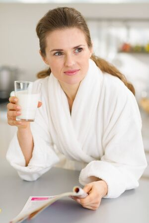 Young woman in bathrobe with milk and magazine Stock Photo - 17800072