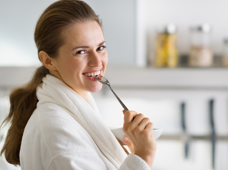 Portrait of young woman in bathrobe eating breakfast in morning photo