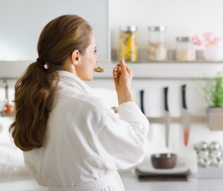 Young woman in bathrobe eating breakfast. rear view Stock Photo - 17800060