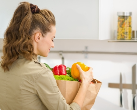 Young housewife examines purchases after shopping in kitchen. rear view Stock Photo - 17800090