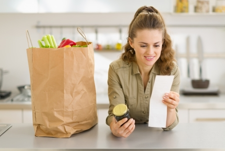Smiling young housewife examines purchases and check after shopping in kitchen Stock Photo - 17800149
