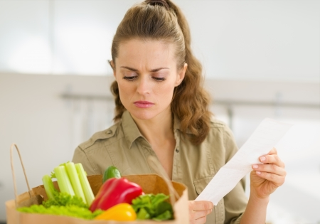 disquieted: Concerned young housewife examines check after shopping Stock Photo