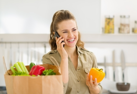 sort: Young housewife sort purchases after shopping and talking mobile phone