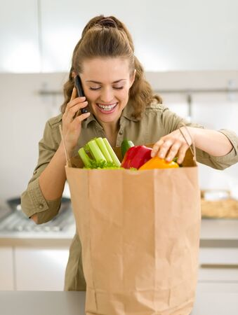 Young housewife sort purchases after shopping and talking cell phone Stock Photo - 17800058