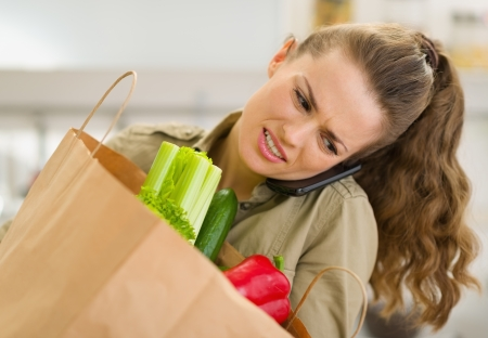 disquieted: Concerned young housewife with big shopping bag talking mobile phone Stock Photo