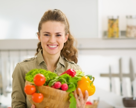 Portrait of smiling young housewife showing plate of fresh vegetables Stock Photo - 17800077