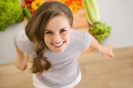 Portrait of happy young woman in kitchen Stock Photo - 17800089