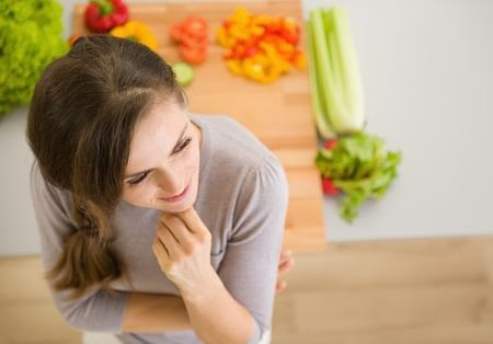 Portrait of thoughtful young woman in kitchen Stock Photo - 17800080