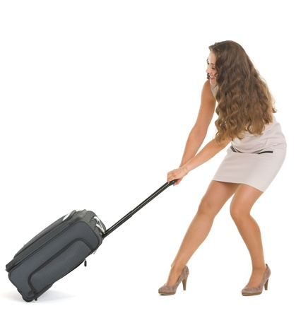 Young traveling woman pulling heavy suitcase on wheels photo