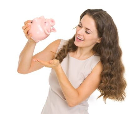 Happy young woman shaking out coins from piggy bank Stock Photo - 17890564