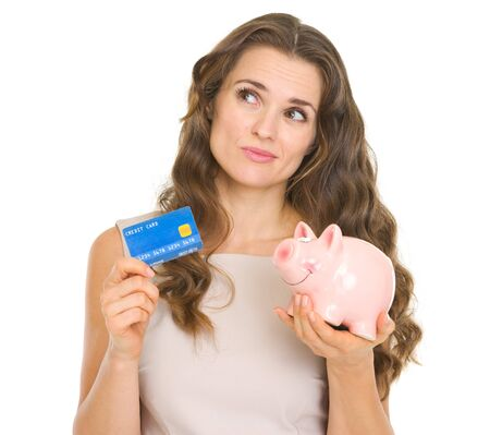 sagacious: Thoughtful young woman holding credit card and piggy bank
