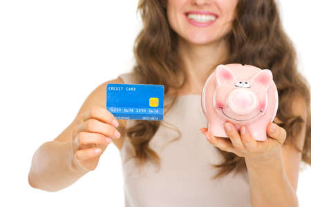 Closeup on woman holding credit card and piggy bank Stock Photo - 17890610