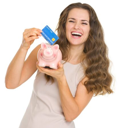 Happy young woman putting credit card into piggy bank Stock Photo - 17890621