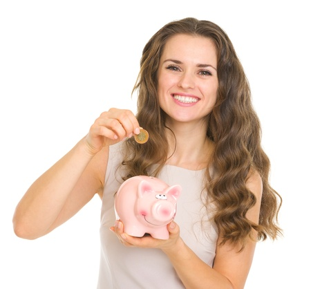 frugality: Happy young woman putting coin into piggy bank Stock Photo