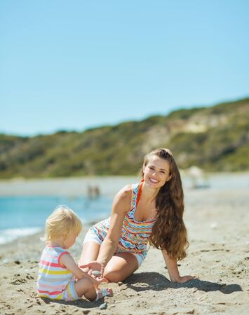 Happy mother and baby girl playing with sand on beach photo