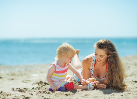 Mother and baby girl playing with sand on beach Stock Photo - 17933971
