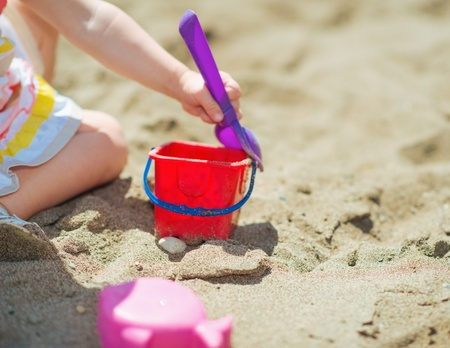Closeup on baby girl playing with bucket and shovel on beach Stock Photo - 17934012