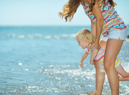 Mother and baby girl playing on sea coast photo