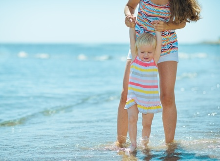 Mother and baby girl playing at seaside Stock Photo - 17934003
