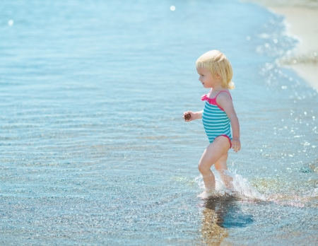 Baby girl walking into sea Stock Photo - 17933984