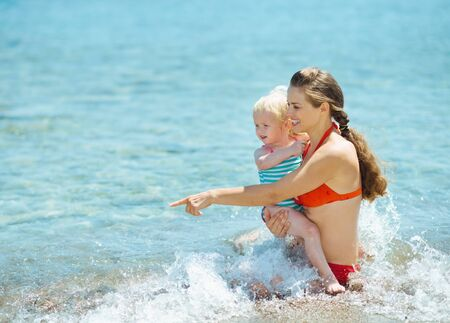 Mother showing something to baby girl at seaside Stock Photo - 17934018