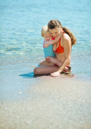 Mother showing something to baby girl on sea coast Stock Photo - 17934022