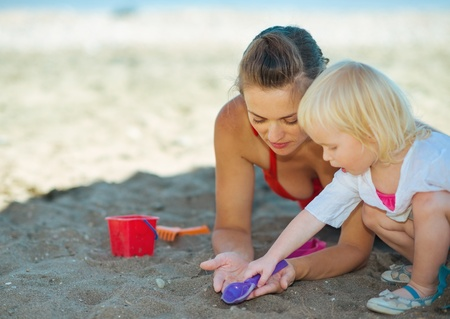 Happy mother and baby girl playing with sand on beach Stock Photo - 17934028