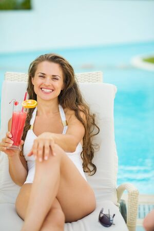Portrait of smiling young woman laying on sunbed and enjoying cocktail Stock Photo - 17933990